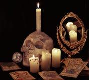 与可怕头骨、灼烧的蜡烛和占卜用的纸牌的静物画在black_1 库存图片