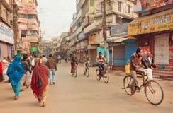 与可怜的人民的街道交通和与城市的骑自行车者的老周期 库存图片