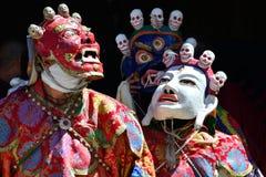 与可汗舞蹈的表现的佛教奥秘在西藏修道院里在Zanskar :与头骨的红色,白色和蓝色面具 免版税图库摄影