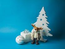 与可爱的圣诞节玩具的蓝色明信片背景 免版税库存照片