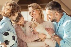 与可爱的拉布拉多小狗的年轻家庭在前面 库存图片