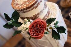与可食的玫瑰色植物布置的时髦婚宴喜饼 蛋糕以与被编织的设计底下排的赤裸顶面排为特色 免版税库存照片