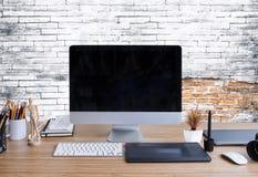 与台式计算机、办公用品和膝部的时髦的工作区 免版税库存图片