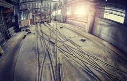 与台车轨道的被放弃的工业大厅内部 免版税库存图片