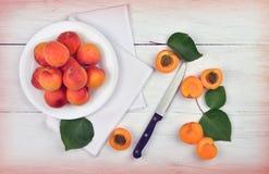 与叶子和一把刀子的杏子在木背景 库存图片