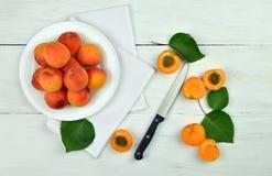 与叶子和一把刀子的杏子在木背景 免版税库存图片