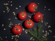 与叶子和南瓜籽的几个红色蕃茄在黑背景 从上面射击 免版税图库摄影