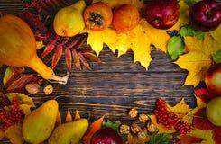 与叶子和收获的秋天背景在年迈的木书桌wi 免版税库存图片