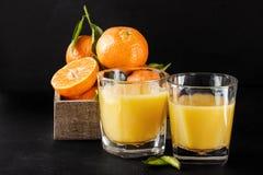 与叶子和汁液玻璃的成熟蜜桔在黑暗的背景 库存照片