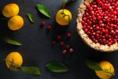 与叶子和蔓越桔的黄色普通话在一个灰色石自由空间的一个篮子 库存图片