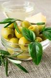 与叶子和迷迭香的橄榄在一块小玻璃 免版税库存照片