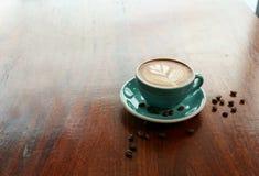 与叶子形状拿铁艺术的热的咖啡在木桌上 库存照片