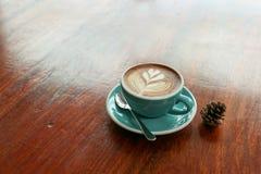 与叶子形状拿铁艺术的热的咖啡在木桌上 免版税库存照片