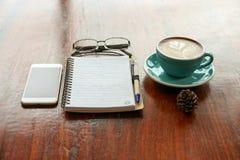 与叶子形状拿铁艺术的热的咖啡在木桌上 免版税库存图片