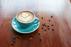 与叶子形状拿铁艺术的热的咖啡在木桌上 库存图片