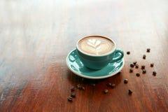 与叶子形状拿铁艺术的热的咖啡在木桌上 图库摄影