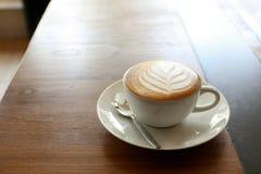 与叶子形状的热的拿铁咖啡在木桌上的白色杯子 免版税图库摄影