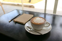 与叶子形状的热的拿铁咖啡在白色杯子、笔记本和铅笔 免版税库存照片