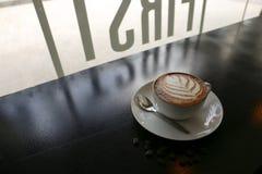 与叶子形状的热的拿铁咖啡在白色杯子用咖啡豆 免版税库存图片