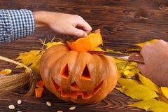 与叶子的一个大秋天万圣夜南瓜在木背景 日历概念日期冷面万圣节愉快的藏品微型收割机说大镰刀身分 免版税库存图片