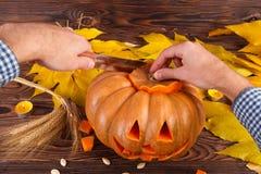 与叶子的一个大秋天万圣夜南瓜在木背景 日历概念日期冷面万圣节愉快的藏品微型收割机说大镰刀身分 库存图片