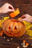 与叶子的一个大秋天万圣夜南瓜在木背景 日历概念日期冷面万圣节愉快的藏品微型收割机说大镰刀身分 图库摄影