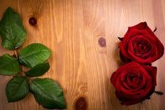 与叶子的两朵华伦泰玫瑰在木头 库存照片