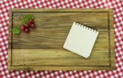 与叶子的五棵樱桃在木板和纸的角落食谱的 免版税库存图片