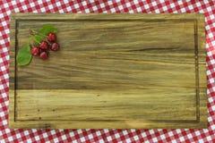 与叶子的五棵樱桃在木板的角落 免版税库存图片
