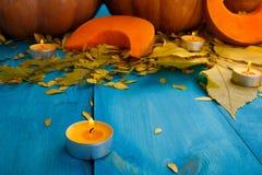 与叶子的大鲜美秋天南瓜在蓝色背景 在倾吐的餐馆沙拉的主厨概念食物新鲜的厨房油橄榄 库存图片