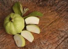 与叶子的新番石榴果子和番石榴切片在木背景 图库摄影