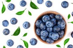 与叶子的新鲜的成熟蓝莓在白色背景隔绝的木碗 顶视图 平的位置样式 免版税库存照片