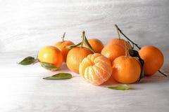 与叶子的新鲜的柑桔,整个和剥皮在浅灰色 免版税库存图片
