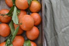 与叶子的新鲜的橘子果子或蜜桔在桌上的木箱 免版税库存照片