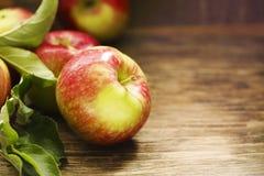 与叶子的新鲜的苹果在木背景 库存图片