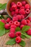 与叶子的新鲜的莓在木桌上的碗 免版税库存图片