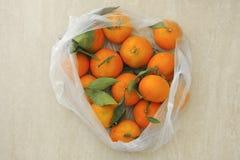与叶子的新鲜的蜜桔在一个塑料袋 库存图片