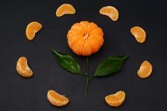 与叶子的新鲜的蜜桔以在黑暗的背景的一朵花的形式 免版税库存图片