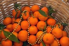 与叶子的明亮的水多的蜜桔在一个柳条筐 金黄G 免版税库存图片
