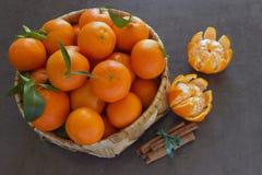 与叶子的明亮的水多的蜜桔在一个柳条筐 Cinnamo 免版税库存照片