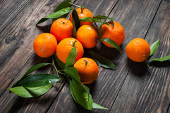 与叶子的柑桔普通话在黑暗的木背景 图库摄影