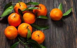 与叶子的柑桔普通话在黑暗的木背景 免版税库存照片