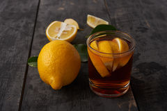 与叶子的柠檬和茶用在一块玻璃的柠檬在一个木选项 免版税库存照片
