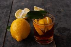 与叶子的柠檬和茶用在一块玻璃的柠檬在桌上 免版税库存照片