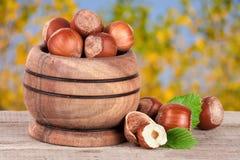 与叶子的榛子在一张木桌上的一个木碗有被弄脏的庭院背景 库存照片