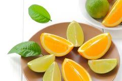 与叶子的橙色切片在白色 图库摄影