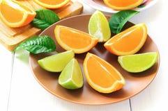 与叶子的橙色切片在白色 库存照片