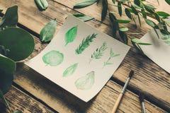 与叶子的水彩绘画在桌上 免版税库存图片