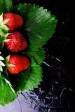 与叶子的湿草莓在黑背景 顶视图 复制空间 免版税库存图片