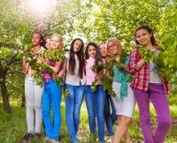 与叶子的美丽的十几岁的女孩举行长凳 图库摄影